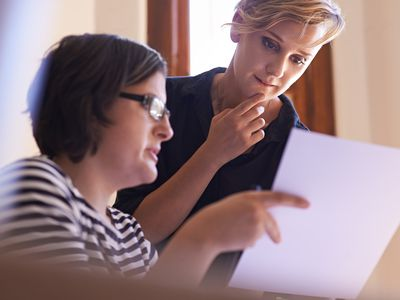 Woman showing a paper to a female tax professional