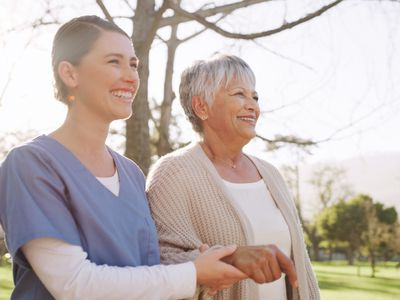 Nurse and older woman walk arm-in-arm in the sun