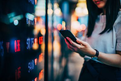 Businesswoman checking financial trading data on smartphone by the stock exchange market display screen board