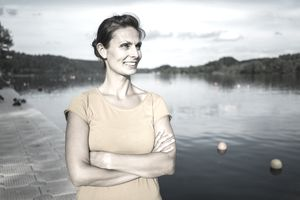 A woman stands next to a lake.