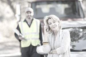 a woman on the phone with a tow truck driver in the background
