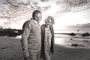 Happy senior couple on beach at sunset