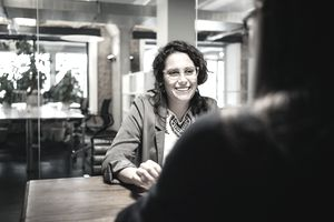 A woman sits at a desk at work and discusses her mutual fund with a coworker.