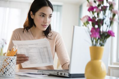 Woman checking account on a computer to see if her electronic check is deposited
