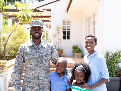 A soldier and his family stand in front of a house