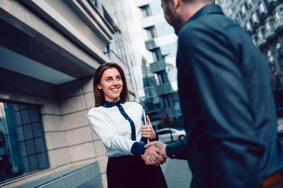 Young businesswoman shaking hands with a man in a suit on a city street