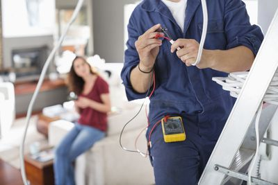 electrician working on home with woman in the background