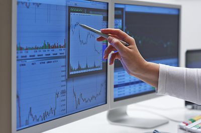 a woman pointing to charts on a a computer monitor
