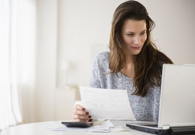 Brunette woman with calculator holds paperwork while looking at laptop