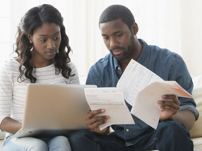 Couple reviewing bills together on a laptop