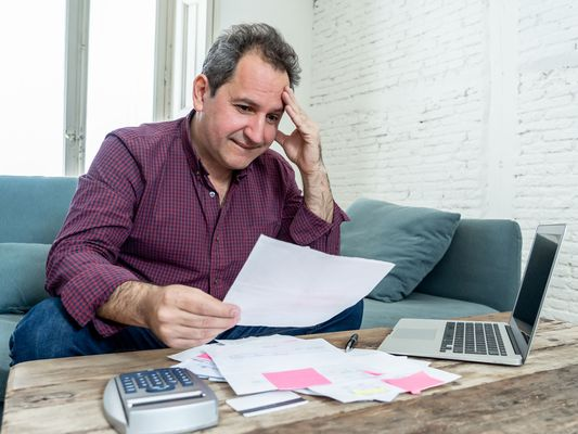 Man Studying Bills With Calculator and Laptop Nearby