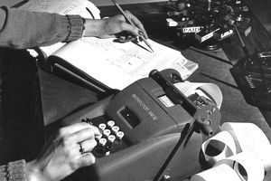 a vintage photo of a woman doing using a large calculator and writing numbers into a general ledger book