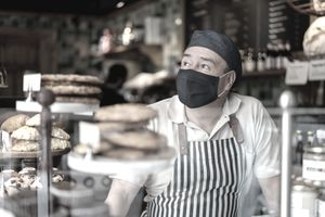 Man working at a coffee shop wearing a facemask