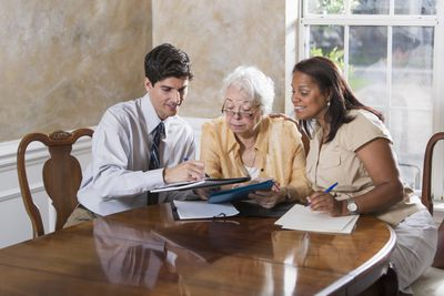 Woman getting advice on creating a POD account at dining room table with advisors