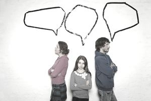 Family with young girl (8-9) standing against wall with blank speech bubbles