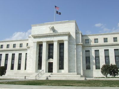 View of the central facade of the Marriner S. Eccles Federal Reserve Building in Washington DC. The flag flies brightly above and a blue sky completes the background. Strong white pillars frame the entry to the building. No people/tourists are in the picture.