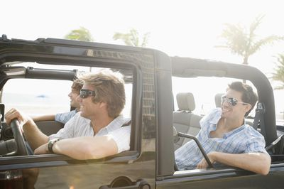 Friends riding in a jeep down Florida highway