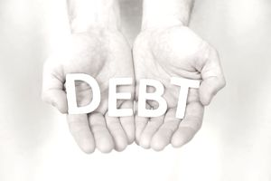 "Hands holding uppercase letters that spell out the word ""debt"""