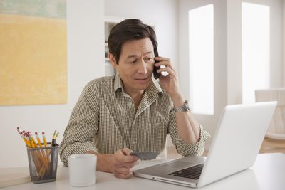 Man looking at laptop and reviewing his credit card information over the phone