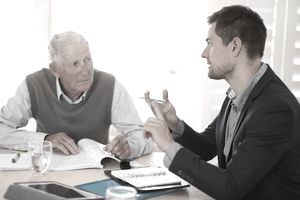 A male lawyer explaining options to an elderly client