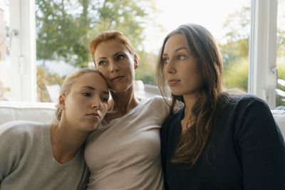 Mother with two teenage girls on couch at home