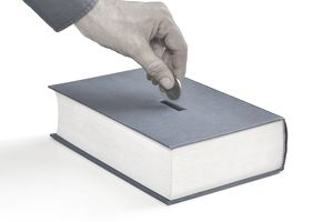 a hand depositing a coin into a slot in a book