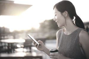 Young Asian woman sitting on bench outdoors, drinking coffee and using smartphone