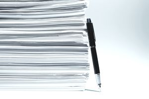 Closeup of an upright pen leaning against a tall stack of documents