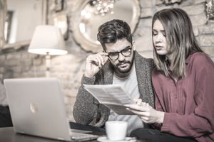 Young Couple Looking Concerned While Reading Paperwork at Laptop on Coffee Table