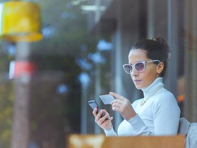Young woman at cafe using credit card for online transaction