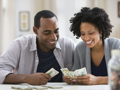 Couple counting money at a table at home