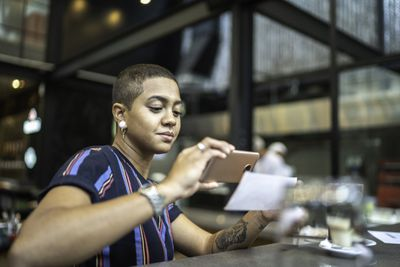 A young woman deposits a check via smartphone app while seated at an outdoor cafe.