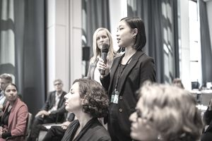 Young businesswoman asking question of a speaker during a stakeholder meeting.