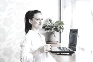 Woman in white shirt holding a cup, smiling in front of her phone and laptop