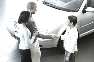 couple shaking hands with a woman after she sells them a car