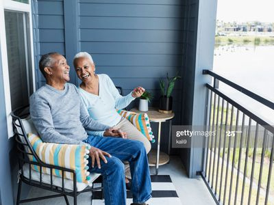 Laughing older couple seated on the porch of their home, overlooking waterway