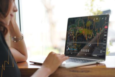 Woman looking at a stock market graph on a laptop screen
