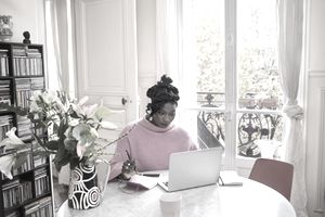 person in bright pink sweater writing something in notebook in a sunny room