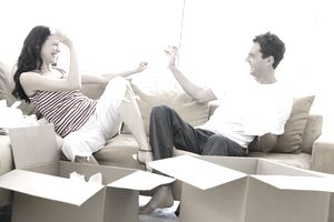 Couple playing on the couch while unpacking