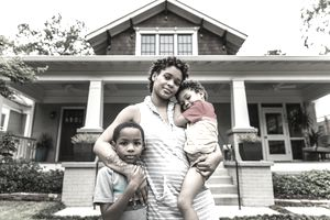 Portrait of single mother with young sons in front of house