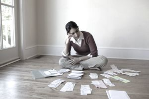 Woman sitting on the floor with head in hand surrounded by stacks of bills and receipts.