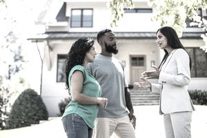 A couple discuss upcoming escrow procedures with their real estate agent in the yard front of the two-story house they may buy.