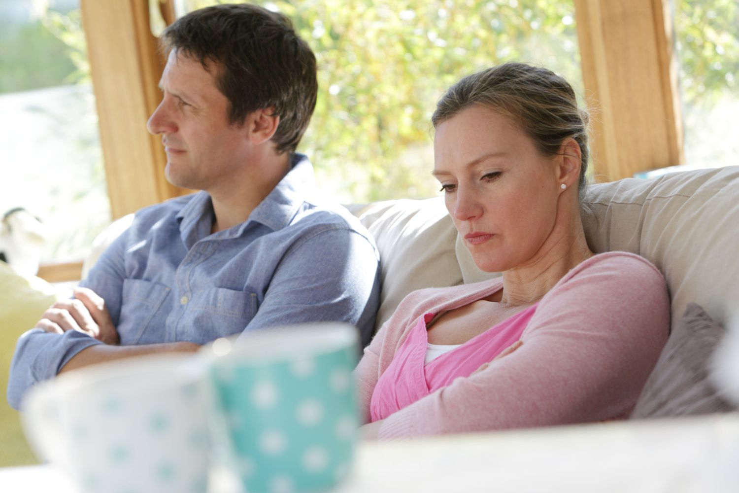 Couple looking away from each other with arms folded