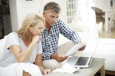 Mature couple looking at financial paperwork in their living room