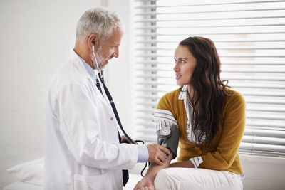 Physician checking woman's blood pressure