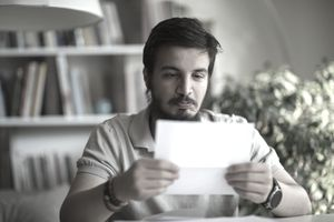 Person in a polo shirt reads a piece of mail