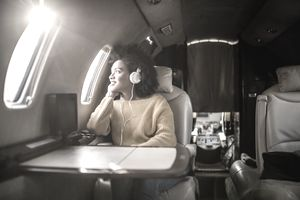 young woman sitting in a first-class seat, looking out an airplane window