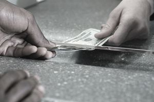 Closeup of bank teller's hand giving cash to a customer