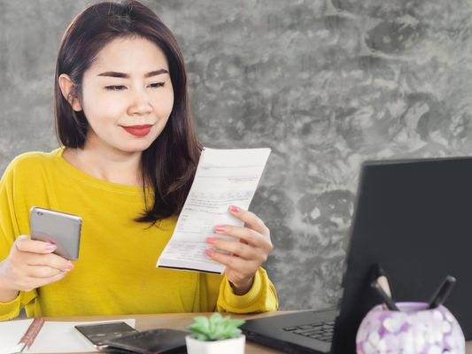 Happy woman viewing electricity bill and smart phone