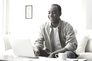 Man Looking at Laptop on Coffee Table in a White Room.